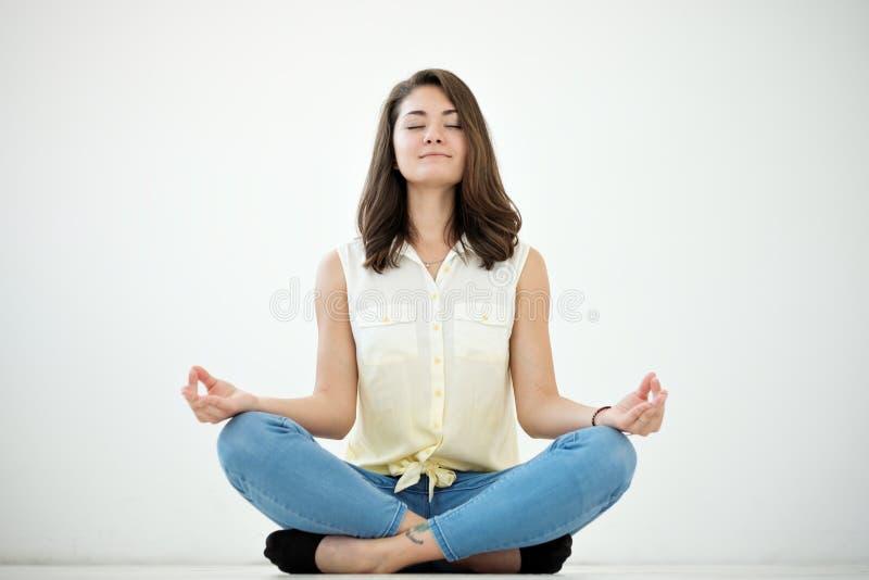 Portret przypadkowa ładna kobieta medytuje na podłoga na białym tle obraz royalty free