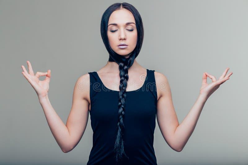 Portret przypadkowa ładna kobieta medytuje na szarym tle obrazy royalty free