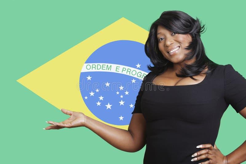 Portret przypadkowa mieszana biegowa kobieta trzyma out pustej palmy nad brazylijczyk flaga fotografia stock