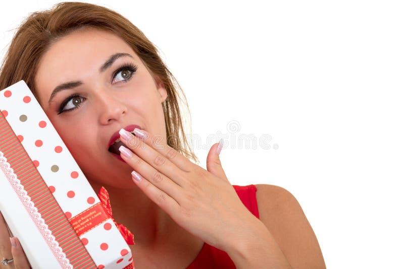 Portret przypadkowego młodego szczęśliwego uśmiechniętego kobieta chwyta prezenta czerwony pudełko Odosobniony pracowniany tło ko fotografia royalty free