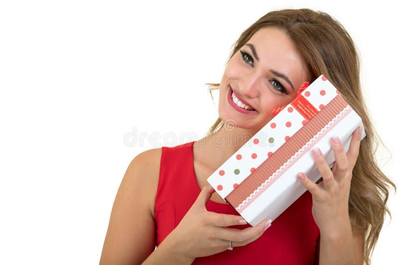 Portret przypadkowego młodego szczęśliwego uśmiechniętego kobieta chwyta prezenta czerwony pudełko Odosobniony pracowniany tło ko obraz stock