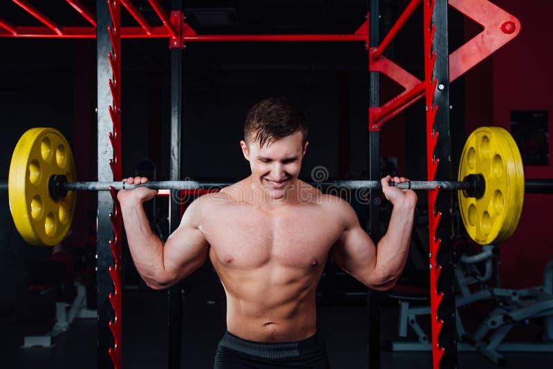 Portret przystojna atleta przy gym mężczyzna robi ćwiczeniu z barbell, pozycją i kucaniem, duży ufny obraz stock