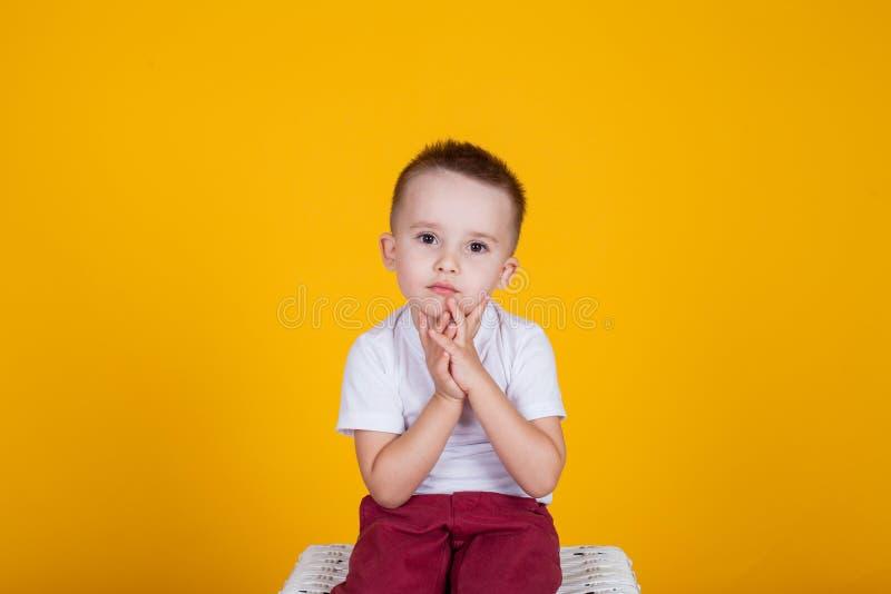 Portret przystojna chłopiec na żółtym tle i cztery roku, obraz stock