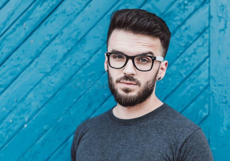 Portret przystojna młody człowiek pozycja przeciw błękitnemu drewnianemu tłu Kultura Młodzieżowa barbershop fotografia stock