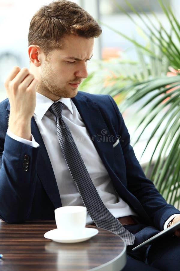 Portret przystojna pomyślna mężczyzna napoju kawa i spojrzenie cyfrowy pastylka ekranu obsiadanie w sklep z kawą zdjęcia royalty free