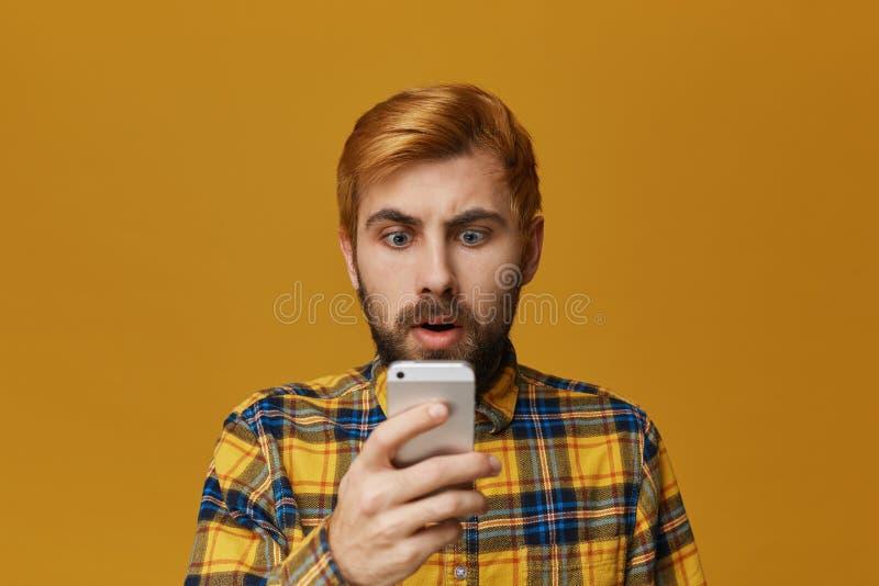Portret przystojna rudzielec farbował zarośniętego mężczyzna, spojrzenia szokujący w mądrze telefonie Technologia i emocjonalny p obrazy royalty free