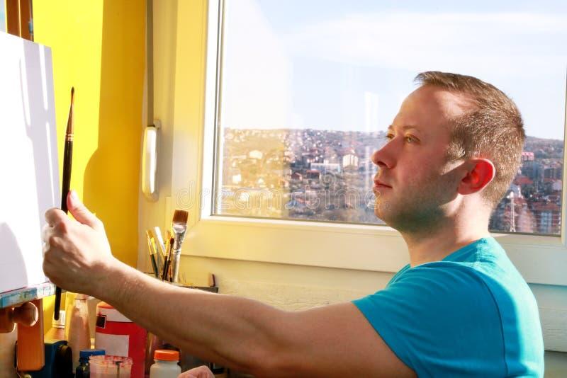 Portret przystojnego artysty pomiarowe proporcje z paintbrush Męski artysty malarz pracuje w warsztacie z kanwą zdjęcie royalty free