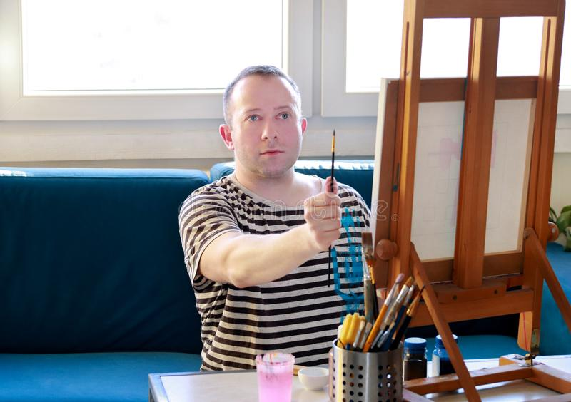 Portret przystojnego artysty pomiarowe proporcje z paintbrush Męski artysty malarz pracuje w warsztacie z kanwą zdjęcia royalty free