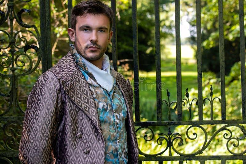 Portret przystojnego dżentelmena ubranego w kostium z rocznika, stojącego na kamiennym dziedzińcu z poręczami w tle fotografia royalty free
