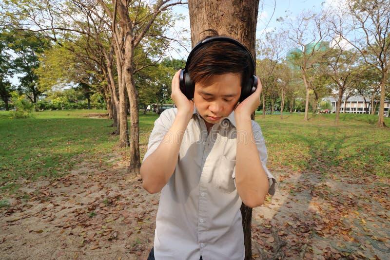 Portret przystojnego młodego człowieka słuchająca muzyka z hełmofonami w parku obraz royalty free