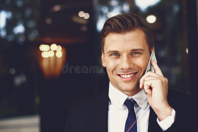 Portret przystojnego uśmiechniętego mężczyzny rozmawiającego przez telefon na zewnątrz obrazy royalty free