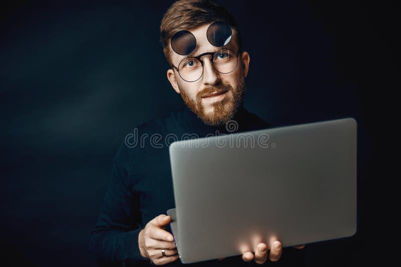 Portret przystojnej brunetki brodaty mężczyzna pracuje w biurowym używa srebnym laptopie obraz royalty free