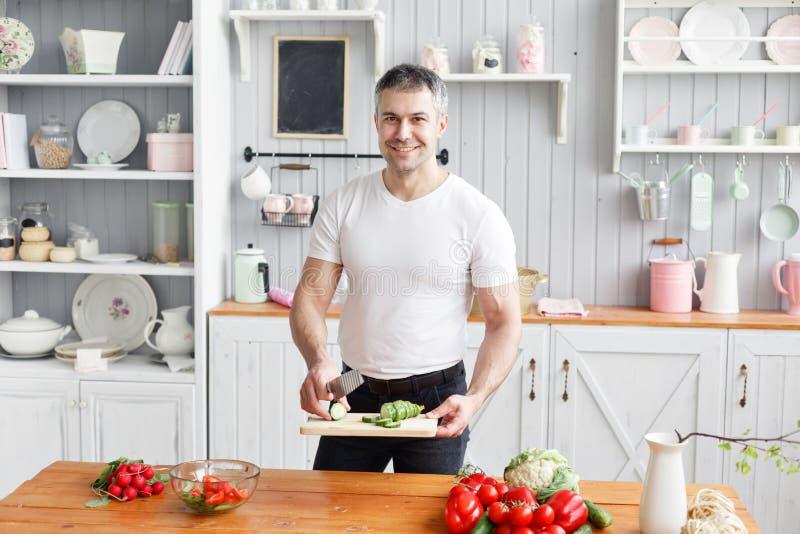 Portret przystojni uśmiechnięci mężczyzny ciapania warzywa w kuchni Pojęcie życzliwi produkty dla gotować obraz royalty free