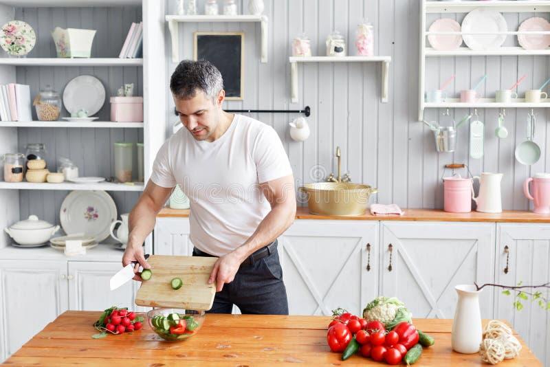 Portret przystojni uśmiechnięci mężczyzny ciapania warzywa w kuchni Pojęcie życzliwi produkty dla gotować obraz stock