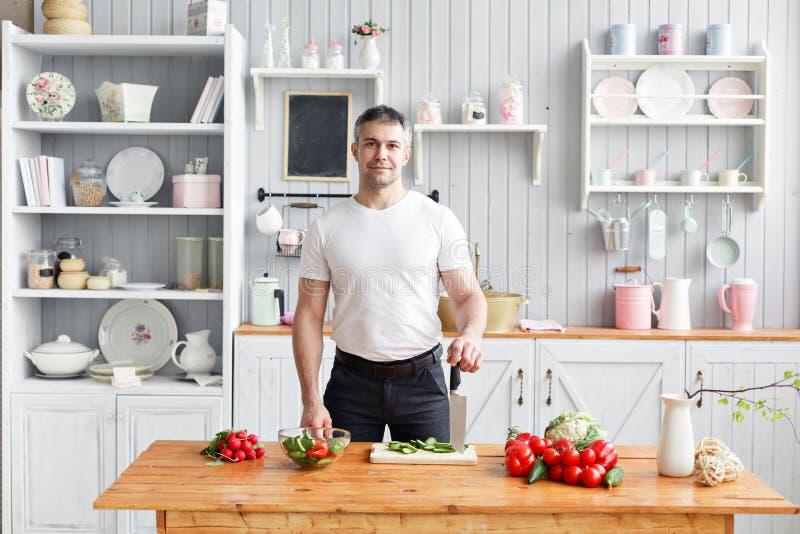 Portret przystojni uśmiechnięci mężczyzny ciapania warzywa w kuchni Pojęcie życzliwi produkty dla gotować obrazy stock