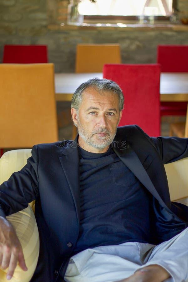Portret przystojny architekta obsiadanie na żółtej kanapie, pionowo fotografia stock