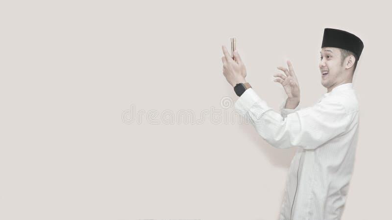 Portret przystojny azjatykci muzułmański mężczyzna z kierowniczą nakrętką i używać smartphone bierze wideo wezwanie i macha uśmie obrazy royalty free