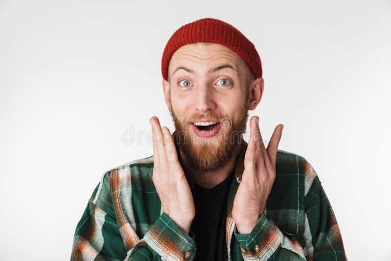 Portret przystojny brodaty facet jest ubranym kapeluszu i szkockiej kraty koszula ono uśmiecha się, podczas gdy stać odizolowywam zdjęcia stock
