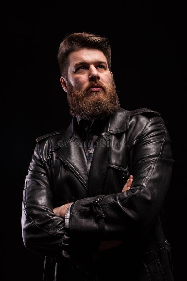 Portret Przystojny brodaty mężczyzna jest ubranym skórzaną kurtkę z poważnym expresion nad czarnym tłem zdjęcia royalty free
