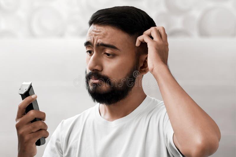 Portret przystojny brodaty mężczyzna trzyma elektryczną żyletkę zdjęcia stock