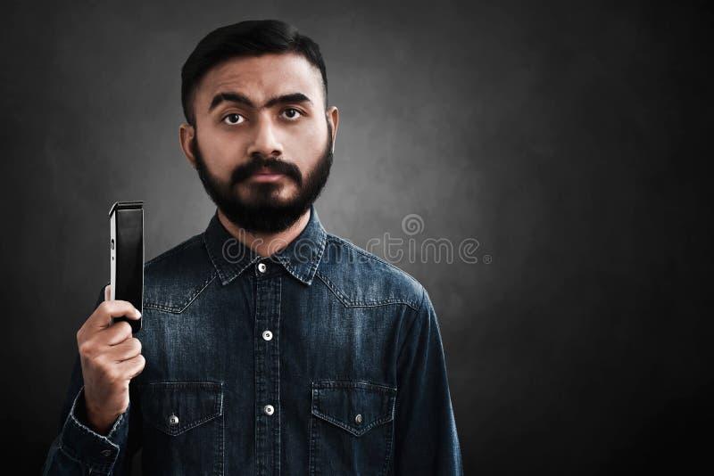 Portret przystojny brodaty mężczyzna trzyma elektryczną żyletkę zdjęcia royalty free