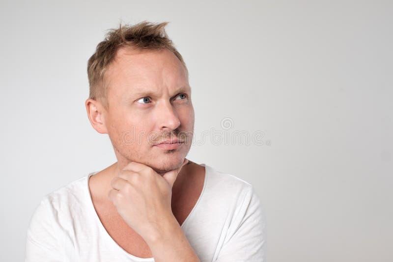 Portret przystojny caucasian mężczyzna patrzeje z wątpliwością up obraz royalty free