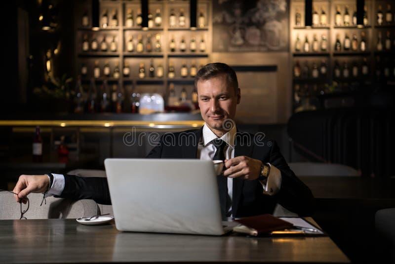 Portret przystojny elegancki caucasian biznesmena obsiadanie przy restauracyjnym działaniem na jego pić kawie i laptopie obraz royalty free