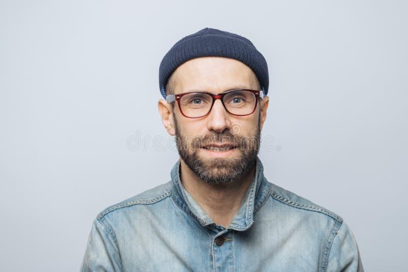 Portret przystojny elegancki męski dziennikarz jest ubranym eyewear, modnego kapelusz i drelich kurtkę, pozy przeciw białemu prac zdjęcia royalty free