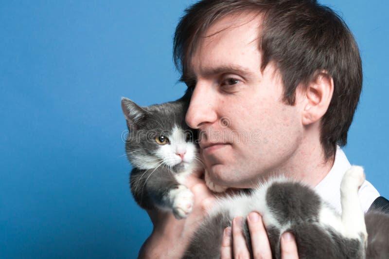 Portret przystojny mężczyzna z przytuleniem i trzymać dalej tylnego ślicznego szarego kota blisko stawiamy czoło obraz royalty free