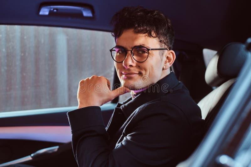 Portret przystojny młody biznesmena obsiadanie w tylnym siedzeniu luksusowy samochód obrazy stock