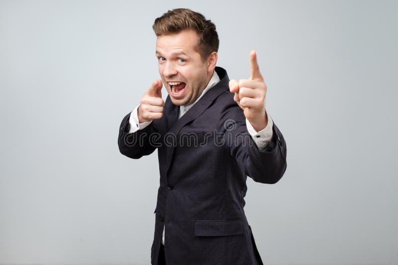 Portret przystojny młody uśmiechnięty mężczyzna wskazuje palce przy kamerą, podnosi ciebie jako zwycięzca zdjęcie stock