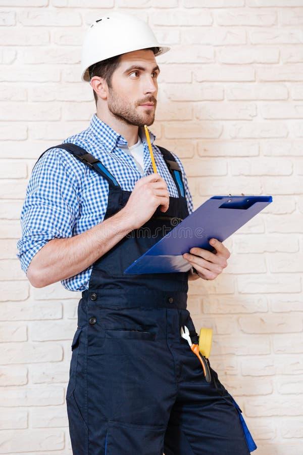 Portret przystojny pracownik używa schowek pisać coś obrazy stock