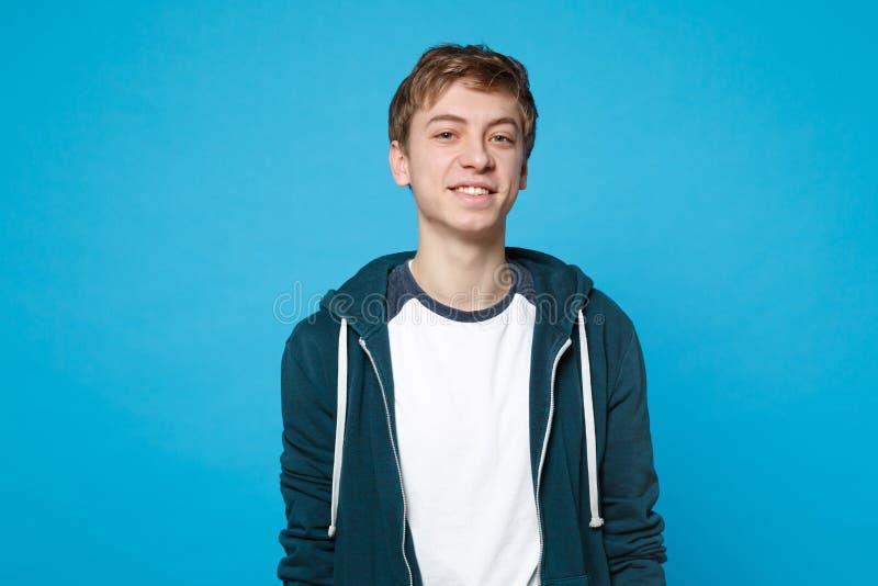 Portret przystojny uśmiechnięty radosny młody człowiek w przypadkowych ubrań stać odizolowywam na błękit ściany tle w studiu obraz royalty free