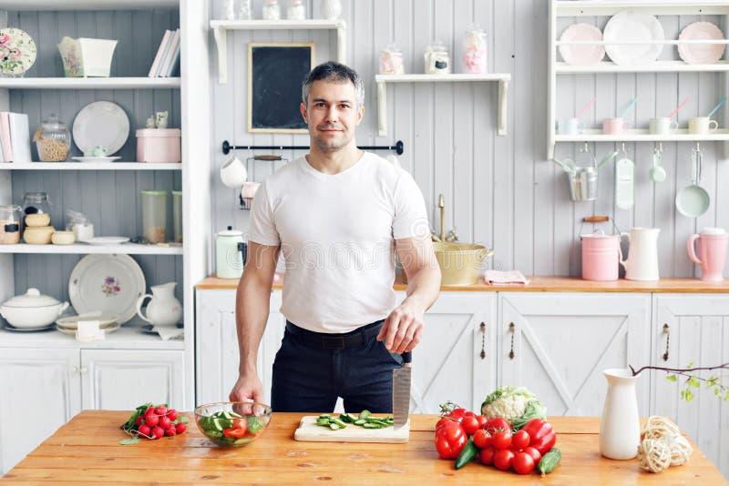 Portret przystojny uśmiechnięty mężczyzna przy kuchnią gotować i domowy pojęcie - zamyka up męski ręki ciapania ogórek dalej fotografia stock