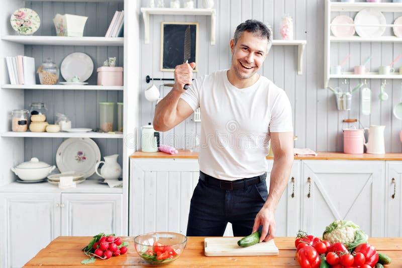 Portret przystojny uśmiechnięty mężczyzna przy kuchnią gotować i domowy pojęcie - zamyka up męski ręki ciapania ogórek dalej zdjęcia royalty free