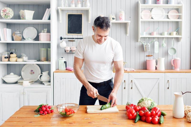 Portret przystojny uśmiechnięty mężczyzna przy kuchnią gotować i domowy pojęcie - zamyka up męski ręki ciapania ogórek dalej fotografia royalty free