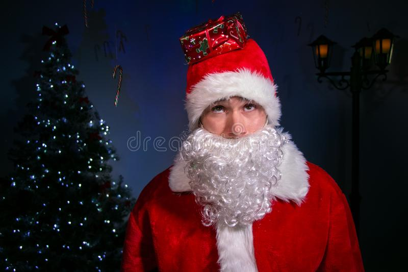 Portret przystojny uśmiechnięty Santa przed choinką z prezentem na jego kapeluszu obraz royalty free