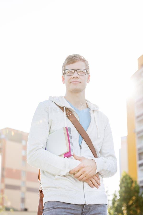 Portret przystojny uczeń z książkami w kampusie przeciw niebu obrazy royalty free