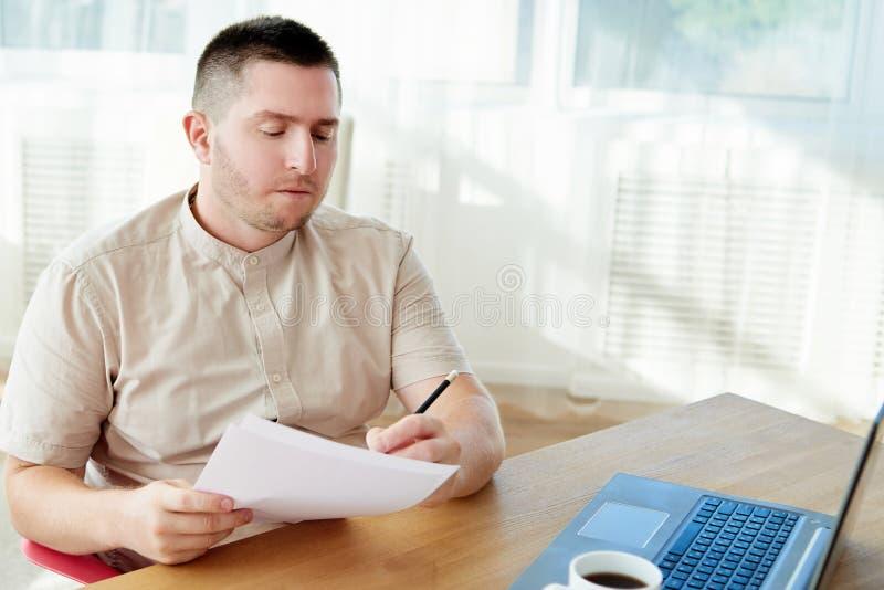 Portret przystojny ufny biznesmena obsiadanie przy drewnianym biurkiem, działanie z dokumentami i laptop w nowożytnym biurze, kop zdjęcie stock