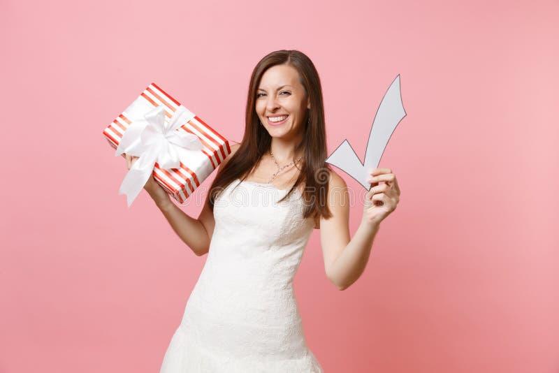 Portret radosna panny młodej kobieta w ślubnej sukni mienia czeka oceny czerwieni pudełku z prezentem, teraźniejszość na różowym  obraz stock