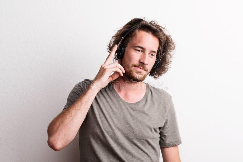 Portret radosny młody człowiek z hełmofonami w studiu fotografia royalty free