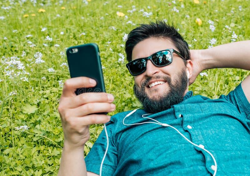 Portret relaksuje na trawie i używa smartphone młody człowiek obraz royalty free