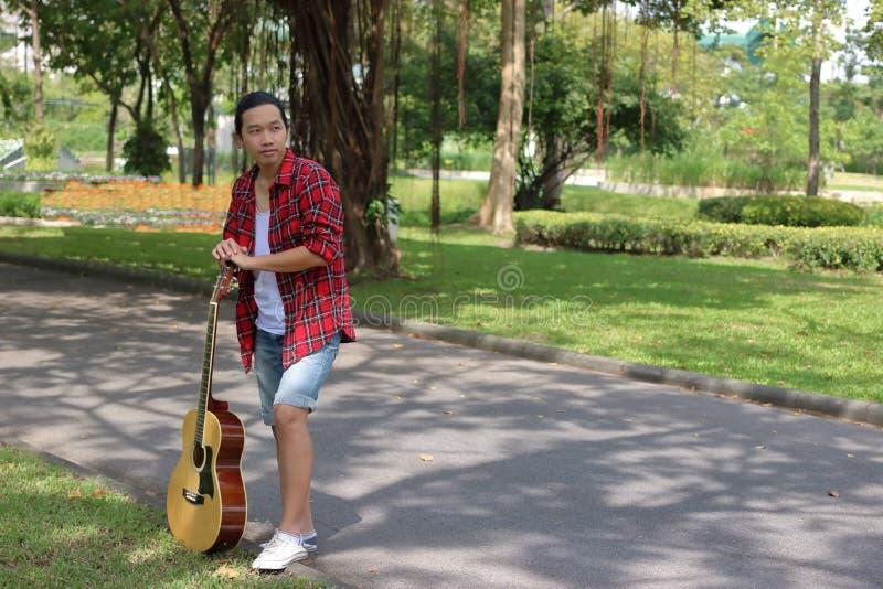 Portret relaksuje przeciw gitarze akustycznej w naturze z kopii przestrzeni tłem gitarzysta fotografia royalty free