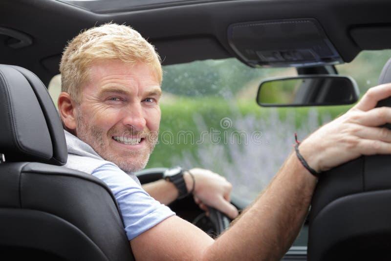 Portret rijpe mannelijke bestuurder die aan achterauto draaien royalty-vrije stock foto's