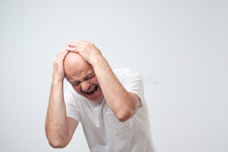 Portret rijpe Spaanse wanhopige mens die zijn hoofd in pijn houden royalty-vrije stock afbeelding