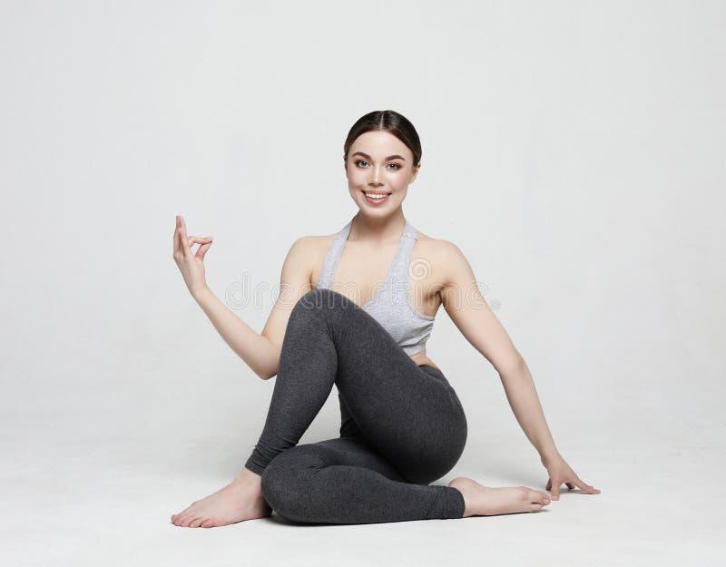Portret robi joga atrakcyjna kobieta, pilates nad jasnopopielatym tłem Zdrowy styl ?ycia i sporta poj?cie zdjęcia royalty free