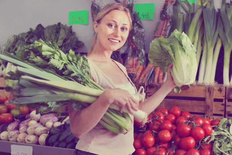 Portret robi zakupy świeżego zielonego seleru, leek i sałaty kobieta, zdjęcia stock