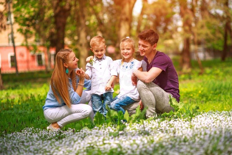 Portret rodzina ma zabawę w kwiatonośnym miasto parku na jaskrawym słonecznym dniu szczęśliwie wydaje ich wolnego czas wpólnie ou zdjęcie royalty free