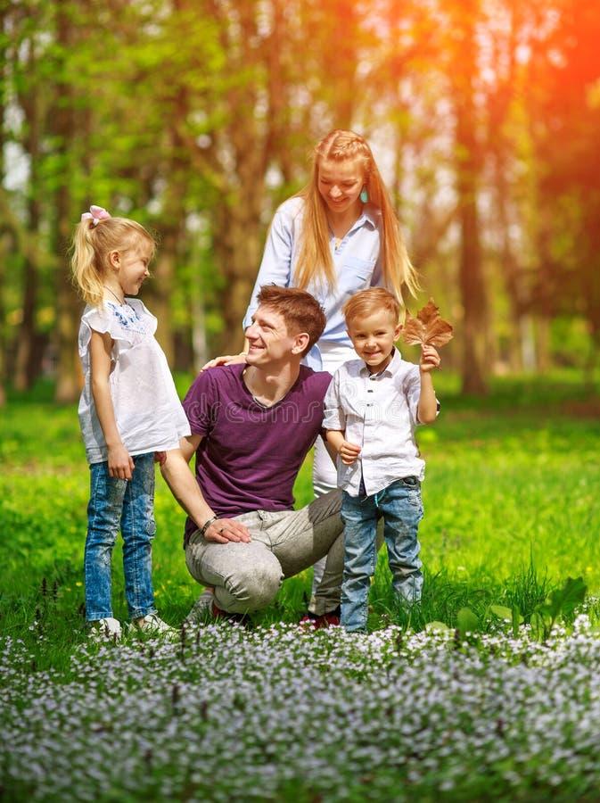 Portret rodzina ma zabawę w kwiatonośnym miasto parku na jaskrawym słonecznym dniu szczęśliwie wydaje ich wolnego czas wpólnie ou zdjęcia stock