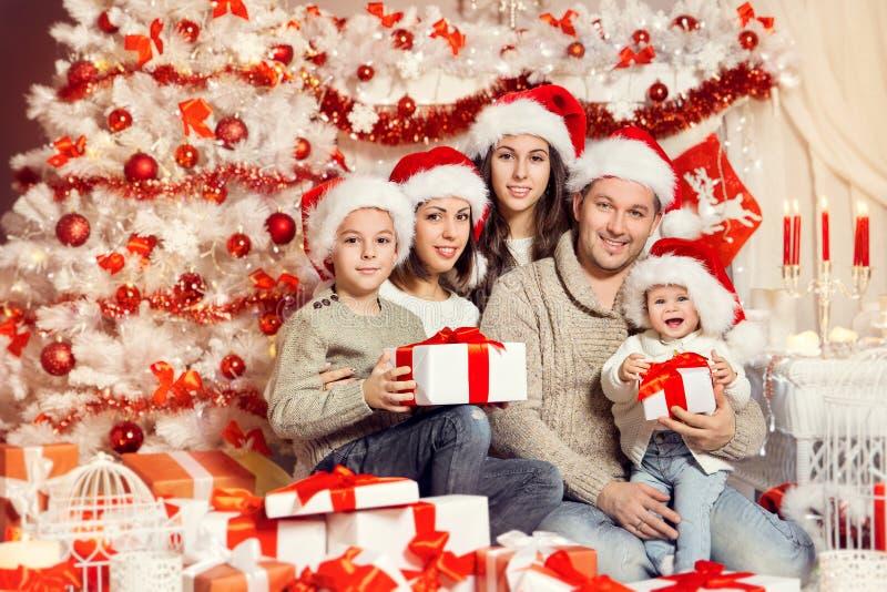 Portret rodziny świątecznej, rodzice z dziećmi w Santa Hats z prezentami w domu, białe drzewo świąteczne zdjęcie stock